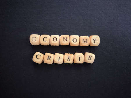 Economic and financial crisis concept. ECONOMY CRISIS written on wooden blocks. Vintage styled background.