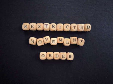 Health and social issues concept. Restricted movement order written on wooden blocks. Blurred vintage styled background.
