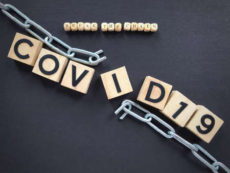 Health care and social issues concept. BREAK THE CHAIN and COVID 19 written on wooden blocks. Archivio Fotografico