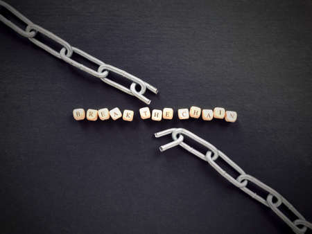 Message and communication concept. BREAK THE CHAIN written on wooden blocks.