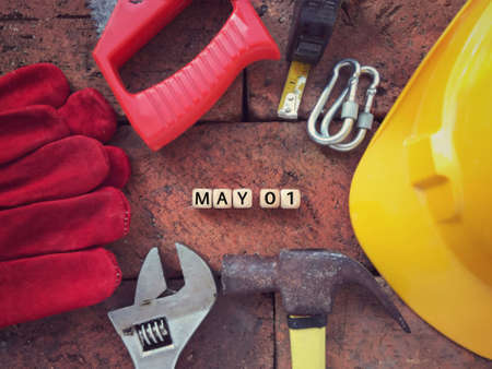 Labor Day concept. MAY 01 written on wooden blocks. With background of working tools.