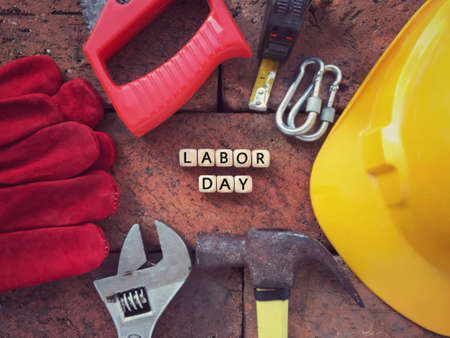 Labor Day concept. LABOR DAY written on wooden blocks. With background of working tools. Archivio Fotografico