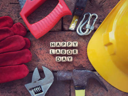 Labor Day concept. HAPPY LABOR DAY written on wooden blocks. With background of working tools. Archivio Fotografico