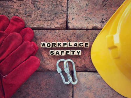 Workplace safety and health concept. WORKPLACE SAFETY written on wooden blocks. Vintage styled background.