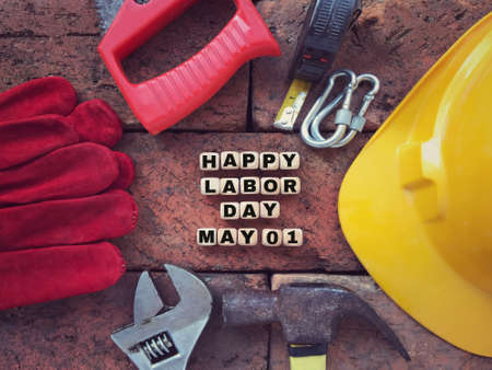 Labor Day concept. HAPPY LABOR DAY and MAY 01 written on wooden blocks. With background of working tools. Archivio Fotografico