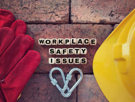 Workplace safety and health concept. WORKPLACE SAFETY ISSUES written on wooden blocks. Vintage styled background.