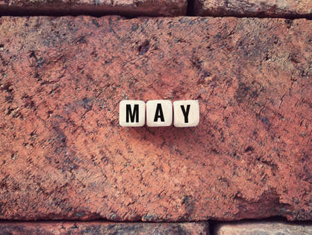 Time and month concept. MAY written on wooden blocks.