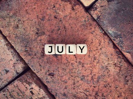 Time and month concept. JULY written on wooden blocks.