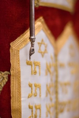 when: Close up of the yad Ð pointer used to read the Torah scroll Ð hanging over the red dress which covers this Torah scroll when not in use. The yad is pointing to an embroidered, gold Hebrew letter reish which decorates the dress.