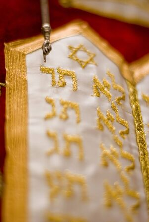 velvet dress: The finger of the yad (hand) points to the gold, embroidered, Hebrew letter dalet on the red, velvet dress which covers the holy Torah scrolls.