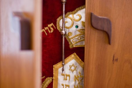 The doors of a wooden ark are beginning to open and reveal the holy Torah draped in a red dress and adorned with silver and gold decorations inside.