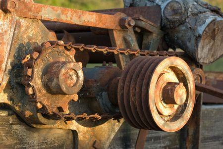 pulleys: Engranajes, cadenas y poleas, oxid�ndose en una vieja pieza de equipo industrial.