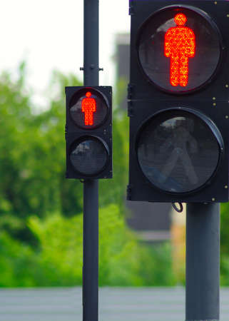 image of two red traffic lights on the background of trees Stock Photo