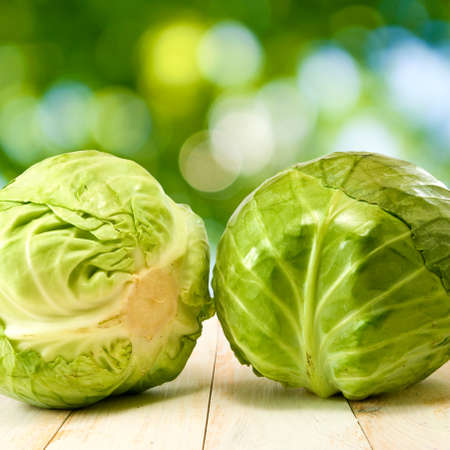 image of cabbage on wooden table on green background photo