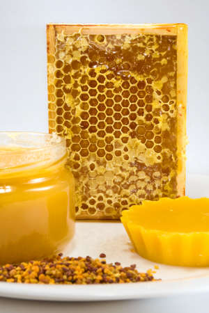 cluster house: image of honey, honeycomb and pollen on a plate on a white background Stock Photo