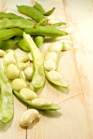 greenbeans: image  of beans in pods on a wooden table closeup Stock Photo