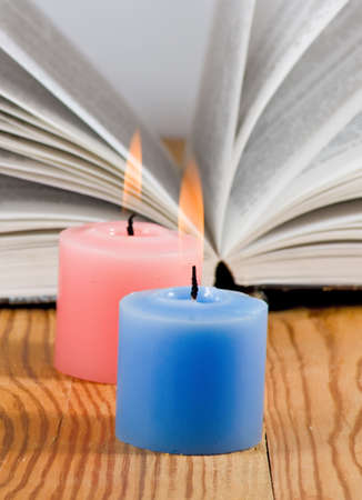 firestarter: image of two candles on open book background close-up