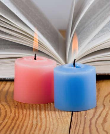 firestarter: two candles on open book background closeup