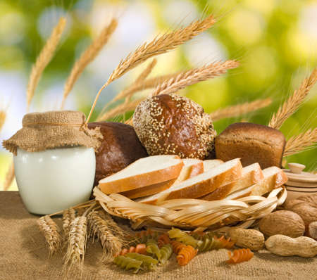 milk products: image of bread, nuts, wheat and dairy on water background