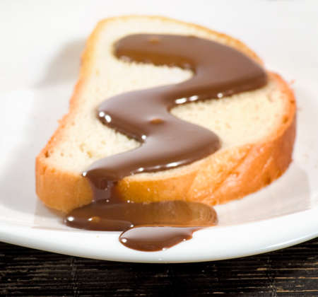 watered: slice of white bread watered with liquid chocolate closeup