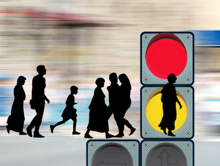 image of silhouettes of people and traffic light closeup