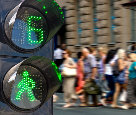 stop and go light: traffic light on people walking background close-up