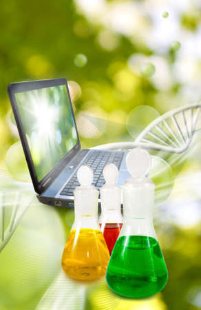 flasks with liquid and laptop in laboratory close up Chemical flasks with reagents on DNA chain background Stock Photo