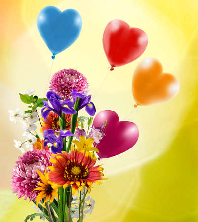 Image of beautiful flowers and colorful balloons on yellow background. Flowers and balloons as a symbol of love and holiday,