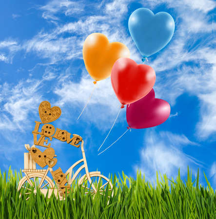 marioneta de madera: Image of decorative little man on a bicycle, balloon against the sky. Wooden man and balloons as a symbol of love and a holiday mood.