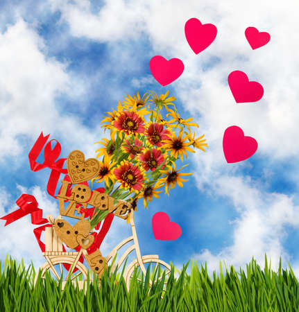 Image of decorative little man on a bicycle against the sky. Wooden man,hearts and flowers as a symbol of love and holiday.