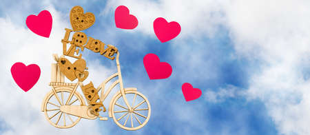 image of stylized toy man on a bicycle and decorative hearts on sky background Stock Photo