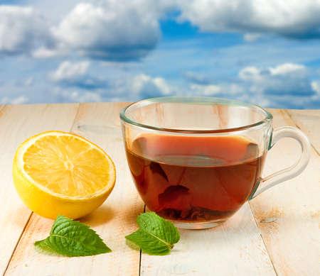 cup with tea, lemon, mint leaves against the sky  Standard-Bild