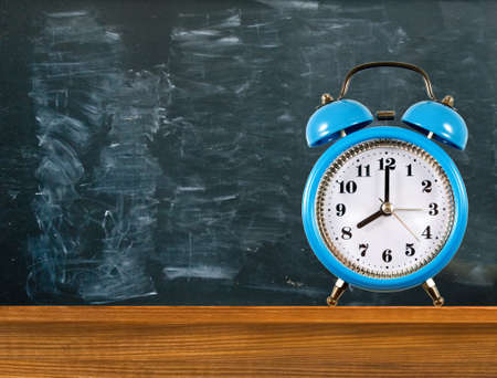 An alarm clock stands on a table against the background of a blackboard with traces of chalk Banco de Imagens