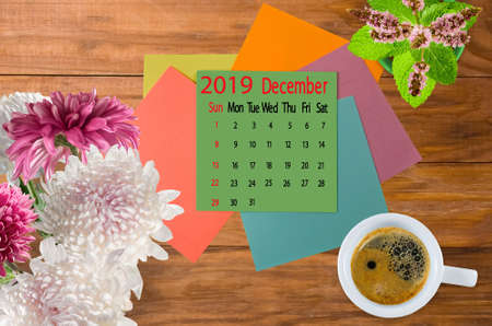 calendar image for December 2019.Coffee, flowers and multicolored pieces of paper on the boards