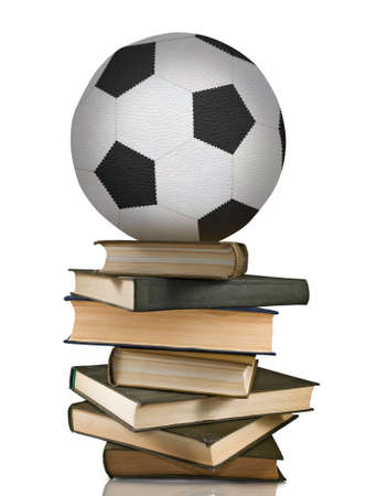 image of a soccer ball that lies on a stack of books 写真素材