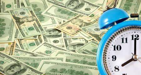 Alarm clock on a background of scattered dollar bills сloseup