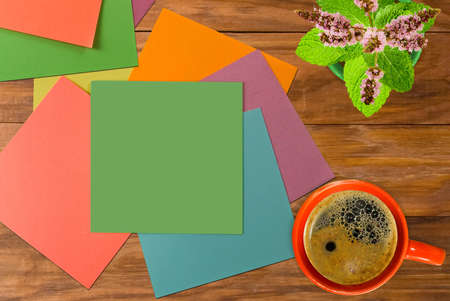Coffee, flowers and multicolored pieces of paper on the boards Imagens