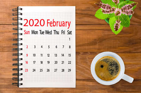 calendar image for February 2020.Coffee, flowers and multicolored pieces of paper on the boards Imagens