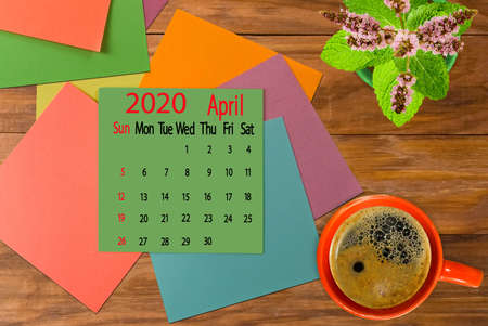 calendar image for April 2020.Coffee, flowers and multicolored pieces of paper on the boards