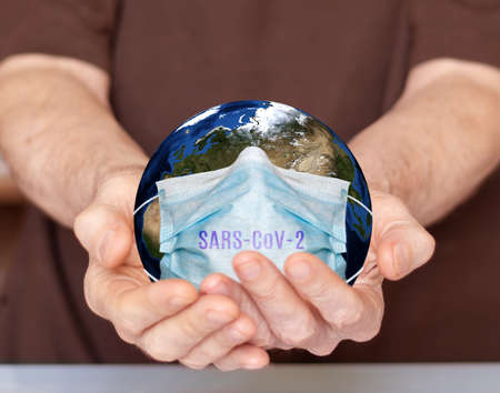 image of planet earth in a medical mask that is between the hands of man Stockfoto