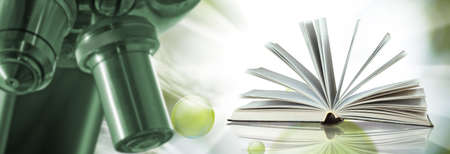 image of microscope, open book on blurred green background Stockfoto