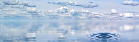 splash on the water that was formed from a drop falling against the background of a panorama of clouds above the water surface Stock Photo