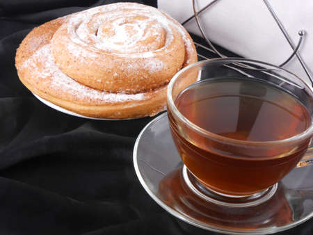 Hot tea with sweet cake on black background photo
