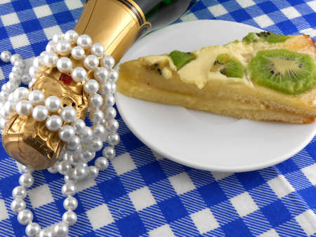 kiwi tasty cake close up at plate, champagne bottle and diamonds photo