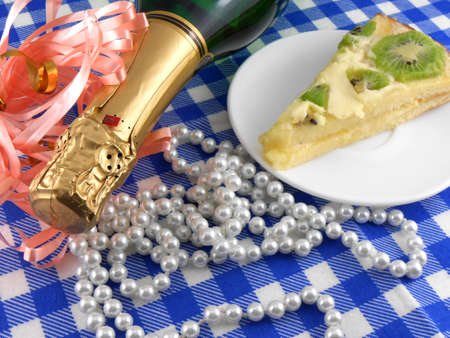 kiwi tasty cake close up at plate, champagne bottle and flowers photo