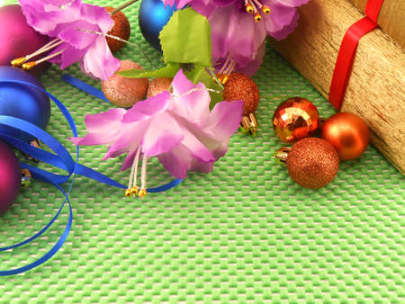 beautiful flowers, gifts and Christmas balls on green background photo