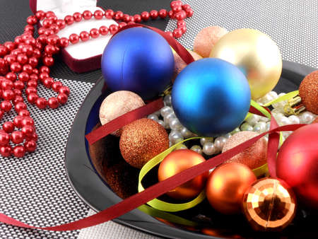 decorative christmas ball and pearls on a plate, new year holiday photo