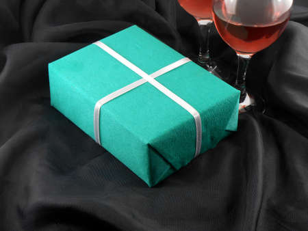 Two champagne glasses and green gift box photo