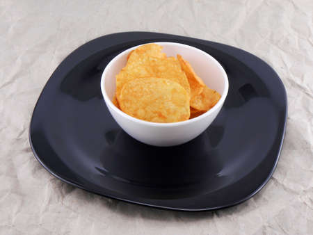 tasty potato chips in white plate on old paper photo