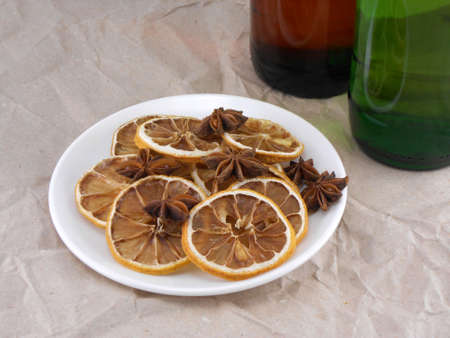 beer bottle with cinnamon and lemon on white plate photo